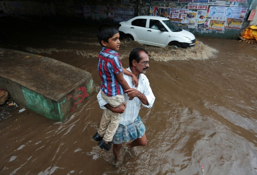 A man carries a child as he wades through a waterlogged subway after heavy rains in Chennai