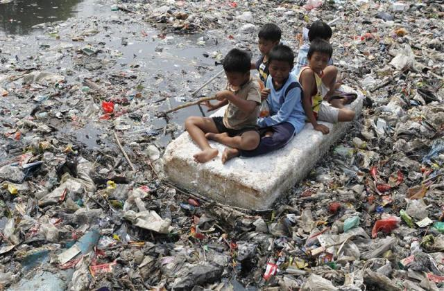 Children sitting on a makeshift raft play in a river full of rubbish in a slum area of Jakarta