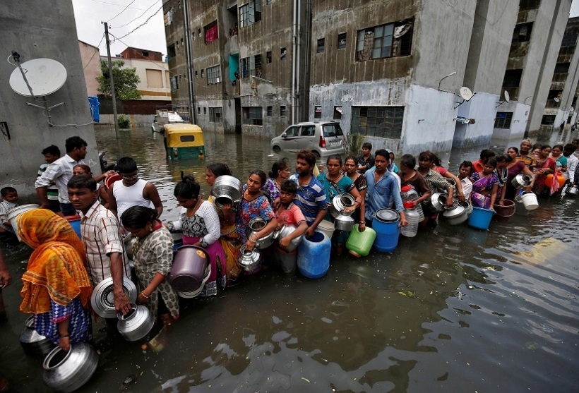 People queue to collect drinking water from a municipal tanker at a flooded residential colony in Ahmedabad