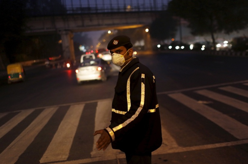 A traffic policeman wears a mask to protect himself from dust and air pollution as he signals to drivers in New Delhi